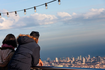 a couple enjoying the view of barcelona, from a high view point