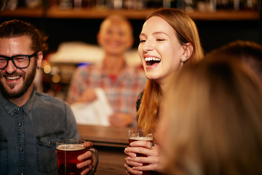 Gorgeous caucasian woman laughing and holding pint of beer while standing at pub surrounded by her best friends.