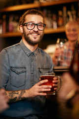 Handsome smiling hipster man sitting at pub near bar counter, holding pint of beer and listening...
