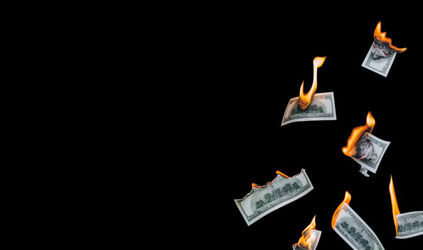 Several 100 dollar bills, falling down, burn on a black background. The concept of bankruptcy, depreciation, devaluation, wastefulness and waste of money. Copy space, isolated.