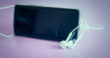 Smartphone and headphones on a light background.