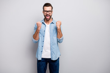 Photo of attractive wild crazy business guy celebrating successful startup project investment yelling raising fists wear specs casual denim outfit isolated grey color background