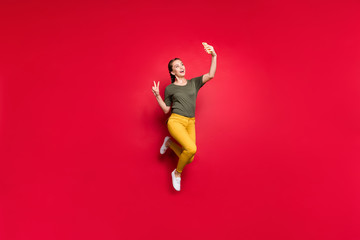 Full body photo of crazy funny lady jumping high making selfies showing v-sign symbol cheerful mood...