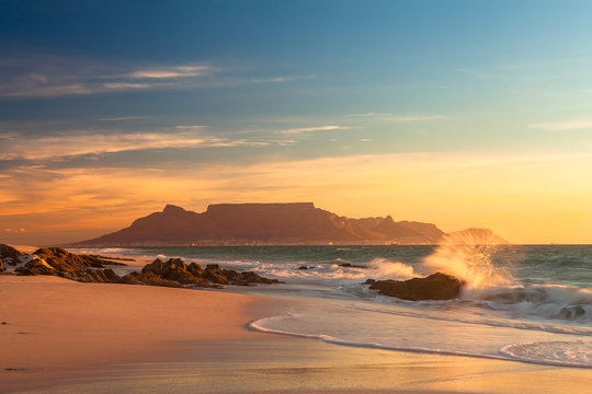 scenic view of table mountain cape town south africa from blouberg at golden sunset with splashing waves