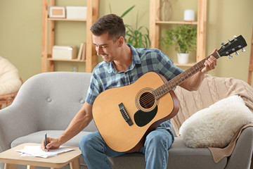 Handsome man with guitar composing music at home