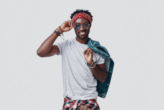 Handsome young African man adjusting his eyewear and looking at camera while standing against grey background