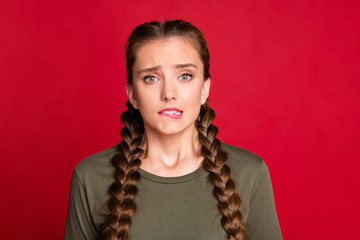 Photo of pretty lady long braids biting lips eyes full of fear uncomfortable situation feel guilty for big mistake wear casual green shirt isolated red color background