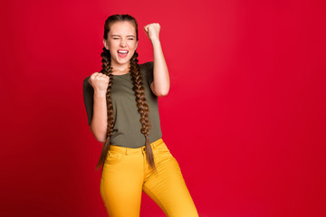 Photo of funny lady long braids raising fists up celebrating best winning football team amazing day wear casual green t-shirt yellow trousers isolated red color background
