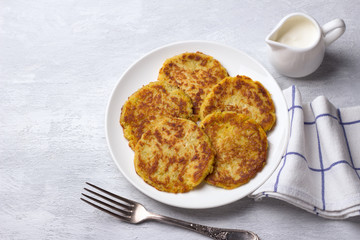 Traditional latkes fritters with sour cream on a light gray textured background with free space, top view