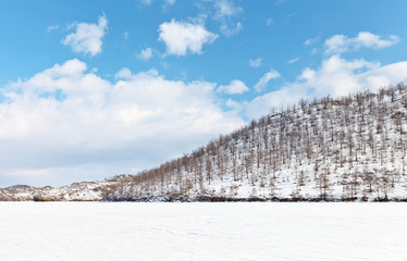 Frozen and snowy Baikal Lake on a February sunny day. Beautiful winter landscape with white hills on the shore of the Kurkut Gulf. Natural background