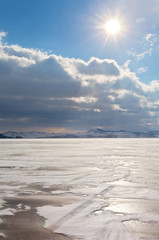 Frozen and snowy Baikal Lake on a February windy day. The sun over the Strait of Small Sea. Winter cold landscape. Natural background