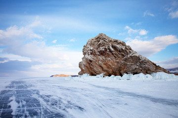 Frozen and snowy lake Baikal on February day. The ice road to Cape Khoboy along the island of Olkhon. View of the small rocky islet of Edor. Beautiful winter landscape