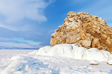 Winter landscape of frozen Baikal Lake. The small rocky islet Edor in the Strait of Smal Sea is popularly called the Head of a Lion. Winter ice travel