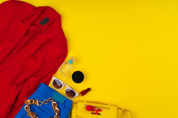 Trendy woman outfit with accessories on bright yellow background