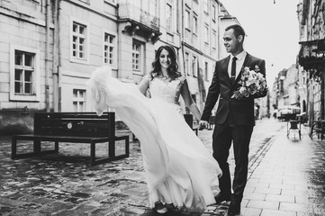 A loving wedding couple are walking along the streets of the city of Lviv. Black and white photo.