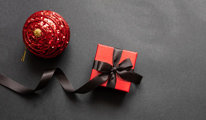 Wall Mural - Christmas present and red xmas ball against black background, Black Friday Christmas concept.