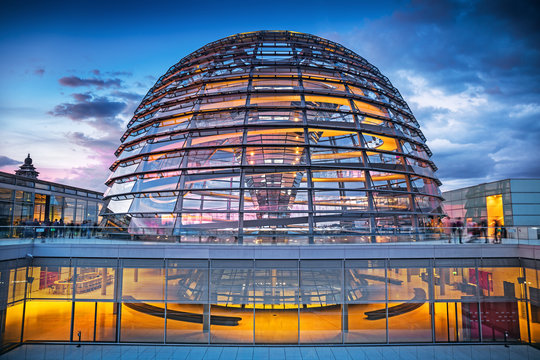 BERLIN, GERMANY - 19 Sep 2019: The rooftop terrace and illuminated glass dome of the Reichstag Building in the evening