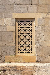 Window with decorative grill made of stone in Icheri Sheher