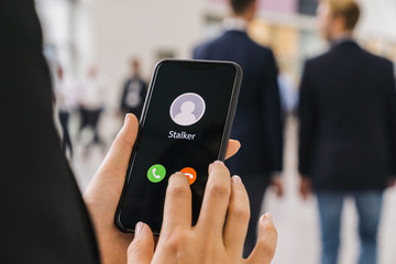 Businesswoman gets a Phone call from a stalker. Stalking or bullying with smartphone concept. Stalker caller, scammer or stranger. Woman answering to incoming call. Ex boyfriend with fake identity.