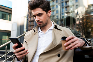 Young confident casual man in trench coat with coffee to go using cellphone on street