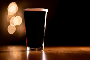 Pint of Dark Stout Beer on a Wooden Table with Copy Space