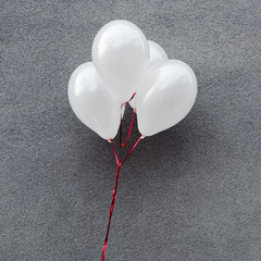 white and decorative party balloons on grey