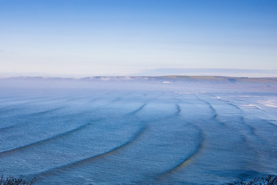 Winter swell arrives at Westward Ho ! Beach in North Devon. Surfers paddle out and catch the waves.