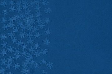 Metallic foil snowflakes confetti sparse on trendy classic blue background. Simple holiday concept. Winter festive backdrop. Top view, flat lay. Color of the year 2020. Copy space for text.