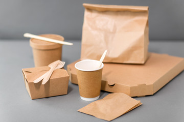 package, recycling and eating concept - disposable paper containers for takeaway food on table