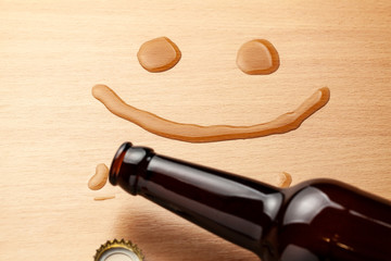 Beer smile. Beer bottle and spilled drink on the table
