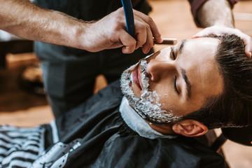 barber shaving bearded man with shaving cream on face