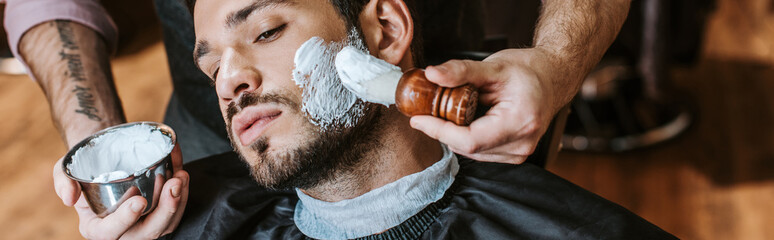 Door stickers Hair Salon panoramic shot of barber applying shaving cream on face of handsome bearded man