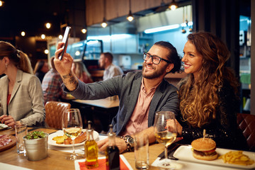 Cute caucasian smiling couple in love sitting in restaurant and taking selfie. Around them are their friends chatting and having dinner.