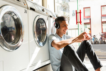 happy North African man sitting on floor leaning against wash machine at laundromat listening to music with cellphone and headphones