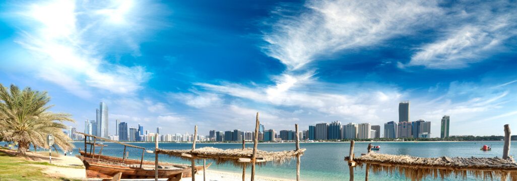 Panoramic view of Abu Dhabi Downtown skyline from the beach at sunset, UAE