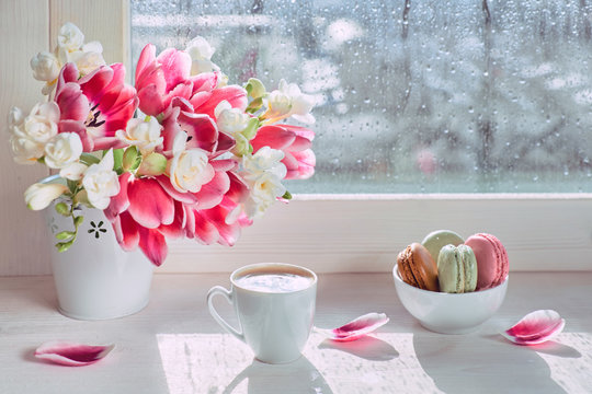Bunch of Spring flowers: pink tulips and white freesia. Pink and green macaroons, tasty sweets to go with espresso. Cup of coffee on the window board, sunshine after rain.