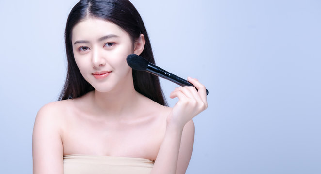 Beauty Asian Girl with Makeup Brushes. She smiling and looking to camera with powder brush, Natural makeup with beautiful v-shape face like korean style