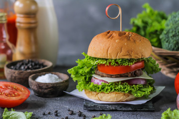 Photo of fresh burger on wooden cutting board on dark background..Homemade hamburger with beef, onion, tomato, lettuce and cheese. Homemade fast food. Dark textured background. Copy space. Image.