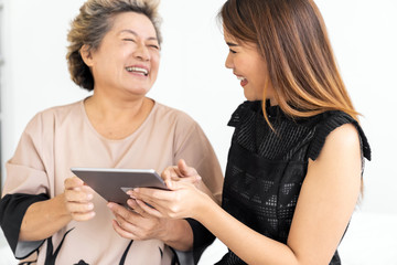 Daughter teaching mother using tablet