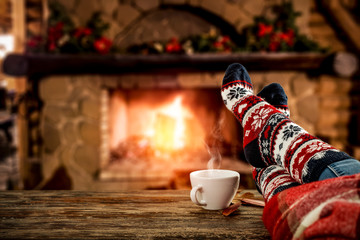 Desk of free space and people legs with christmas socks.Home interior with fireplace and