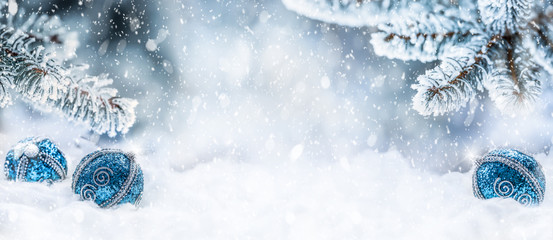Blue christmas balls on snow with fir branches. Merry Xmas concept - panoramic banner