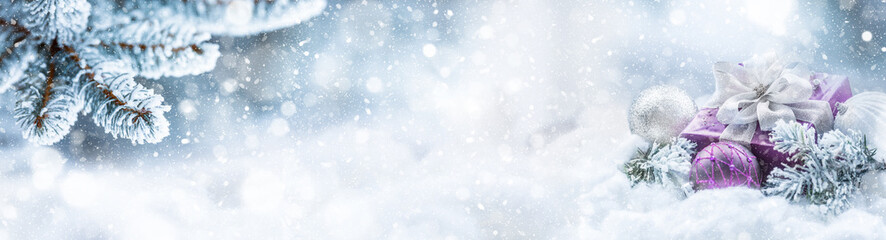 Purple christmas gift and balls on snow with fir branches. Merry Xmas concept- panoramic banner