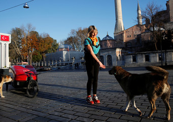Rosie Swale Pope plays with a stray dog as she runs through Istanbul as part of her solo running from London to Katmandu in Istanbul