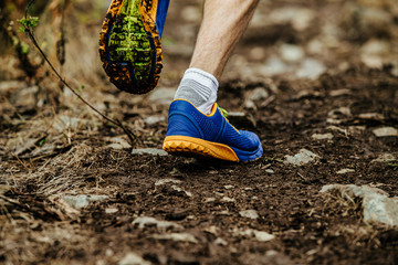 Fototapete - closeup legs running shoes athlete run uphill on muddy trail