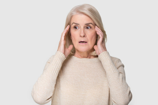 Headshot of aged woman feeling scared isolated on gray background