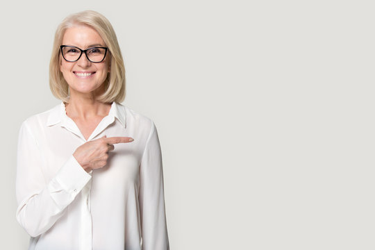 Happy old woman in glasses showing to copyspace blank space