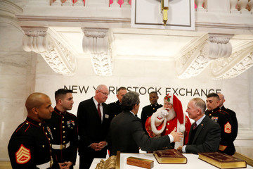 An actor dressed as Santa Claus stands with Henry Osman, CEO of Toys for Tots, and active duty U.S. Marines as they wait to ring the opening bell above the floor of the New York Stock Exchange in New York