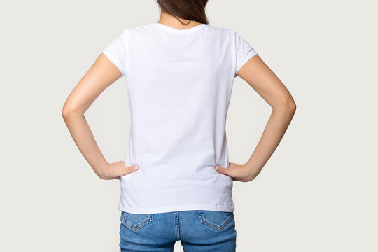 Millennial female wearing white t-shirt standing turning back to camera