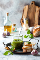 Pesto sauce in glass jar with ingredients.. Basil, olive oil, parmesan, garlic, pine nuts.