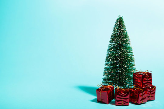 Little Christmas tree with gifts on blue background with copy space